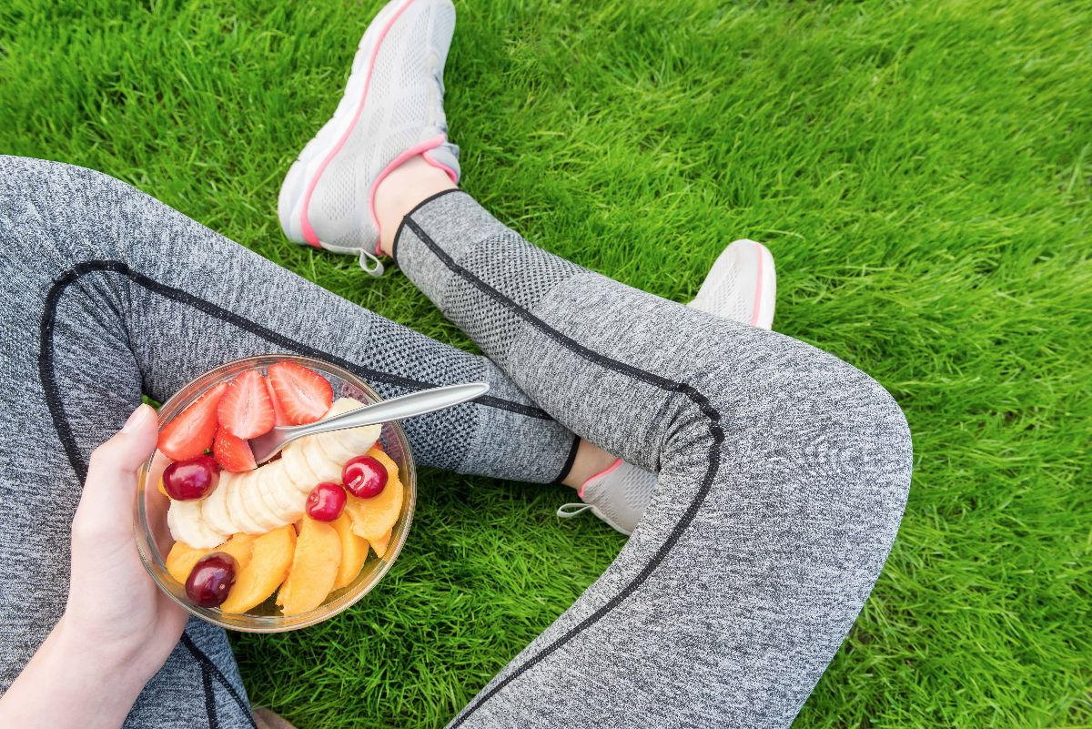 Young girl eating a fruit salad after a workout . Fitness and he